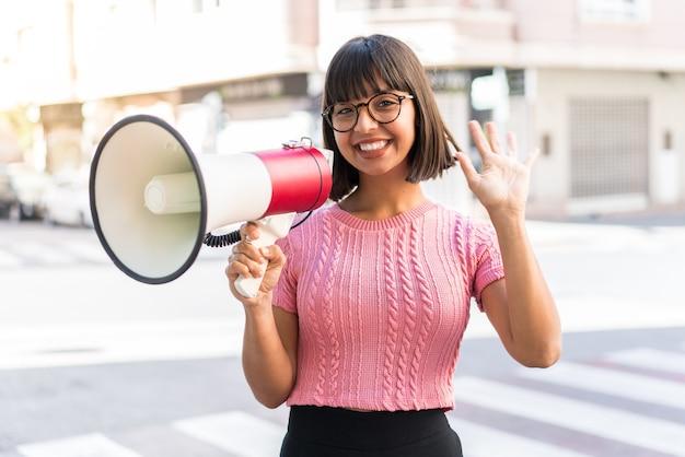 Молодая брюнетка женщина в городе держит мегафон и салютует рукой с счастливым выражением лица
