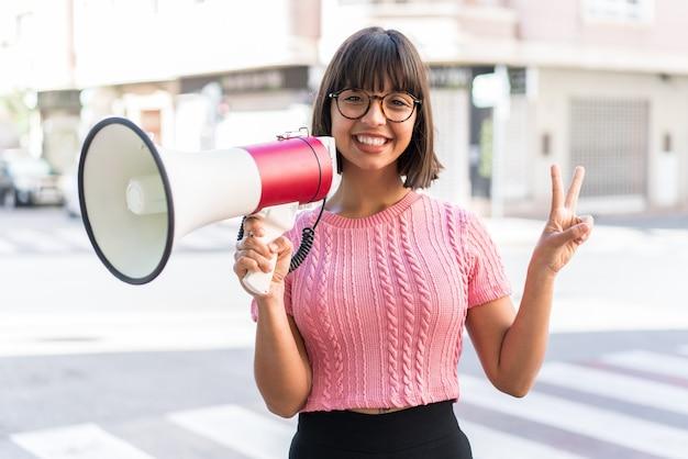 Молодая брюнетка женщина в городе держит мегафон и улыбается и показывает знак победы