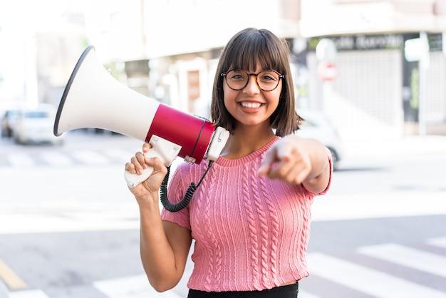 Молодая брюнетка женщина в городе держит мегафон и улыбается, указывая на фронт