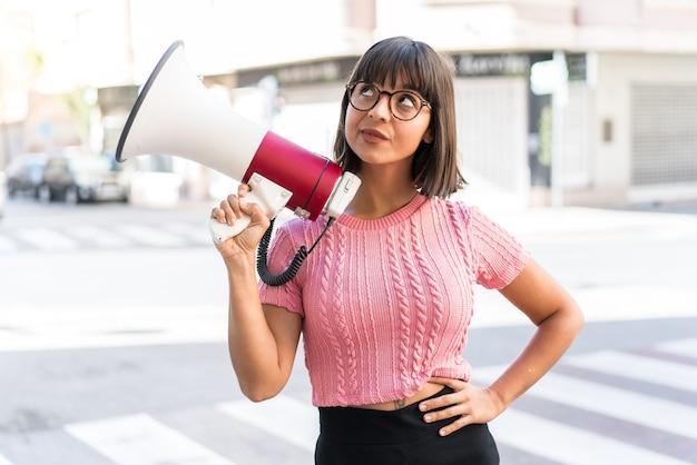 Молодая брюнетка женщина в городе держит мегафон и думает