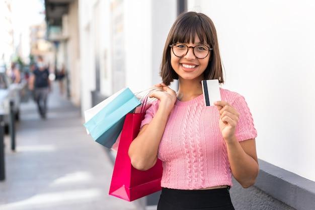 Молодая брюнетка женщина в городе, держащая хозяйственные сумки и кредитную карту