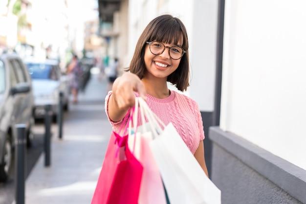 ショッピングバッグを持って誰かにそれらを与える都市の若いブルネットの女性