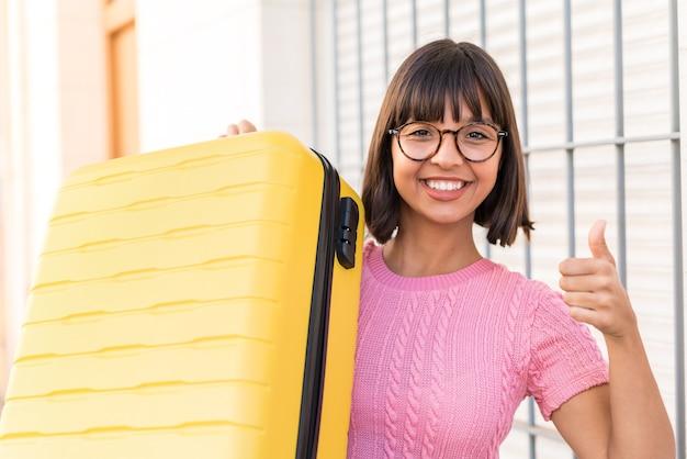 旅行スーツケースと親指を立てて休暇中の街の若いブルネットの女性