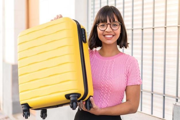 여행 가방과 함께 휴가에 도시에서 젊은 갈색 머리 여자