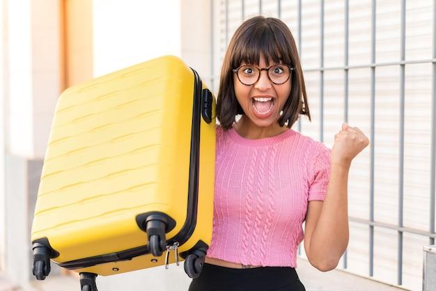旅行スーツケースと休暇で街の若いブルネットの女性