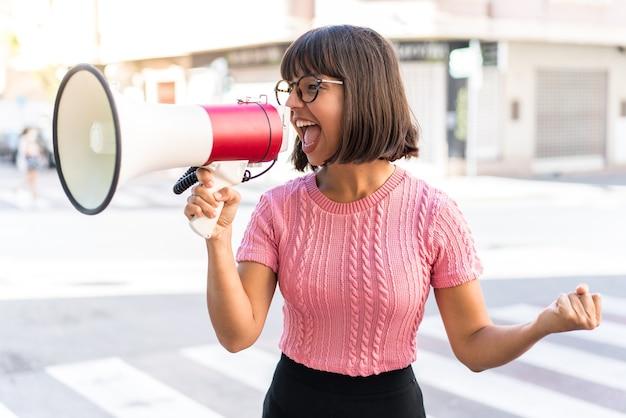 Молодая брюнетка в городе кричит в мегафон, чтобы объявить что-то в боковом положении