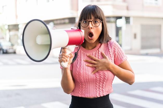 Молодая брюнетка в городе кричит в мегафон с удивленным выражением лица
