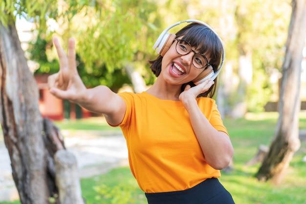 Молодая брюнетка женщина в парке, слушать музыку и петь