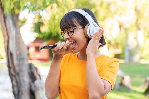 Молодая брюнетка женщина в парке, слушает музыку с мобильного телефона и поет