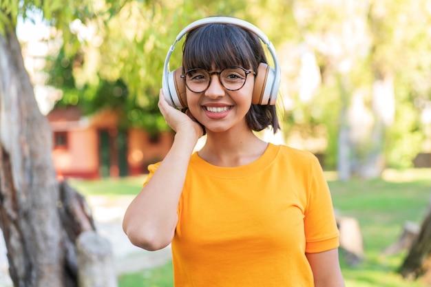 Молодая брюнетка женщина в парке, слушать музыку