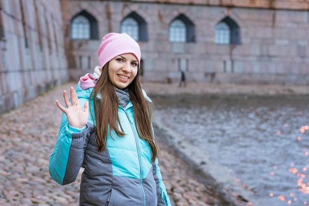 暖かい服とピンクの帽子をかぶった若いブルネットの女性が川のそばに立って、明るい色のアウターウィアに微笑んでいます...