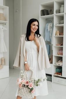 스튜디오에서 꽃의 부케와 흰 드레스와 재킷에 젊은 갈색 머리 여자