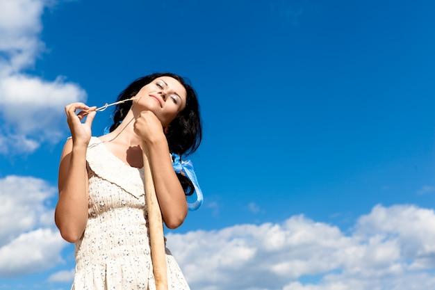 Молодая брюнетка в белом платье стоит с вилами для сена в поле в ясный летний день