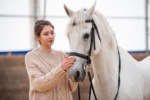 Молодая брюнетка в белом вязаном шерстяном свитере стоит рядом с белым скаковым конем и обнимает ее морду