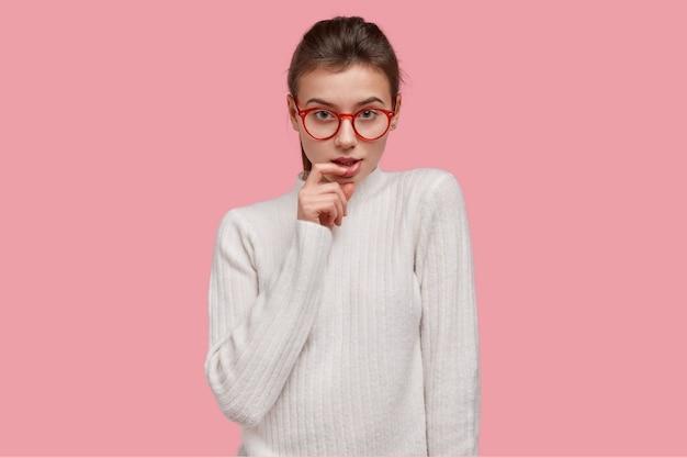 하얀 스웨터와 빨간 안경에 젊은 갈색 머리 여자
