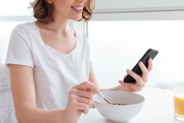 コーンフレークで朝食をとりながらスマートフォンを使用して白いtシャツの若いブルネットの女性