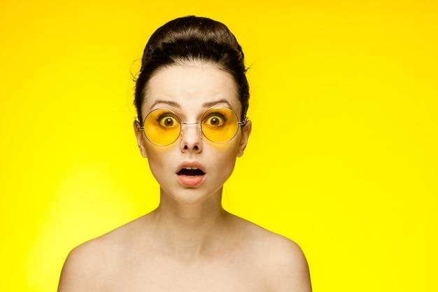 黄色のメガネ、黄色の背景の肖像画の若いブルネットの女性