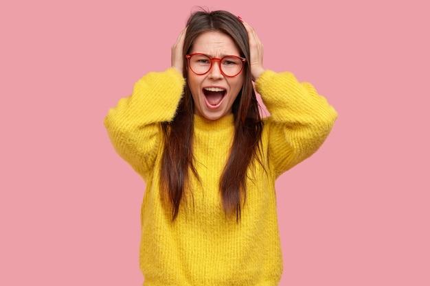 黄色のセーターの若いブルネットの女性