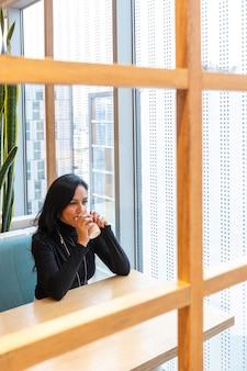 젊은 갈색 머리 여자는 혼자 그녀의 시간을 보내는 동안 커피를 마시고 pensively 거리 바 창 밖을보고있다