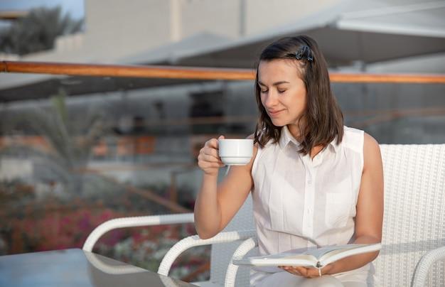 젊은 갈색 머리 여자는 뜨거운 음료 한잔과 그녀의 손에 책과 함께 아침을 즐기고 있습니다. 휴식과 휴식 개념.