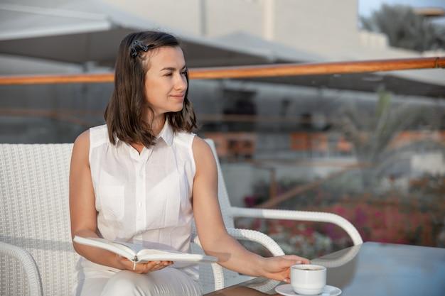 若いブルネットの女性は彼女の手で温かい飲み物と本を持って朝を楽しんでいます。