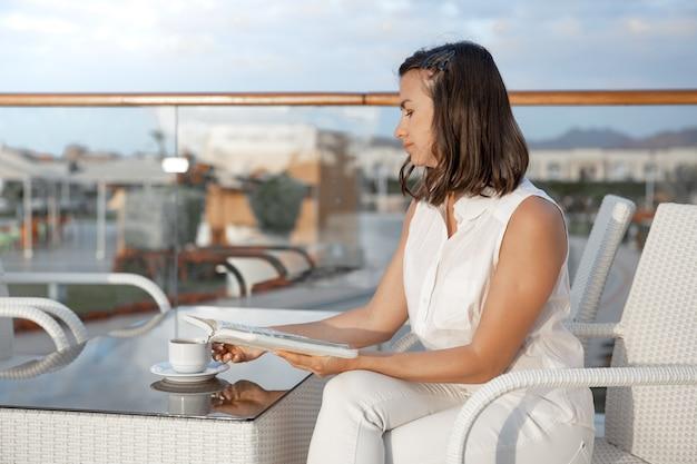 젊은 갈색 머리 여자는 그녀의 손에 뜨거운 음료 한잔과 책과 함께 아침을 즐기고있다