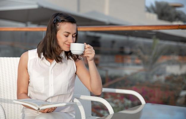 若いブルネットの女性は彼女の手で温かい飲み物と本を持って朝を楽しんでいます