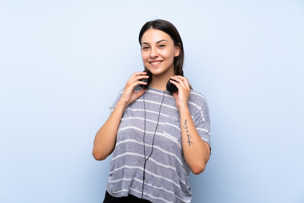 Young brunette woman over isolated blue background listening to music with headphones