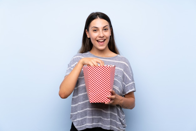 Young brunette woman isolated blue  holding a bowl of popcorns