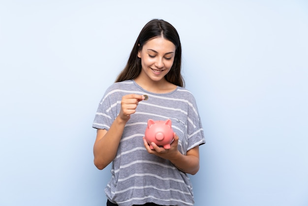 Young brunette woman over isolated blue wall holding a big piggybank
