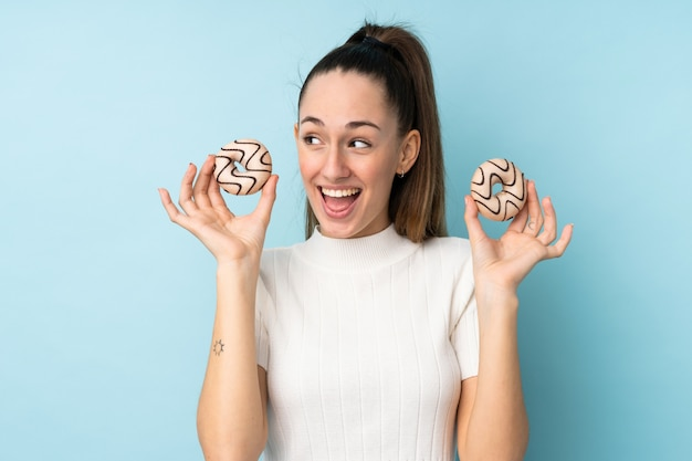 Young brunette woman over isolated blue wall holding donuts and surprised
