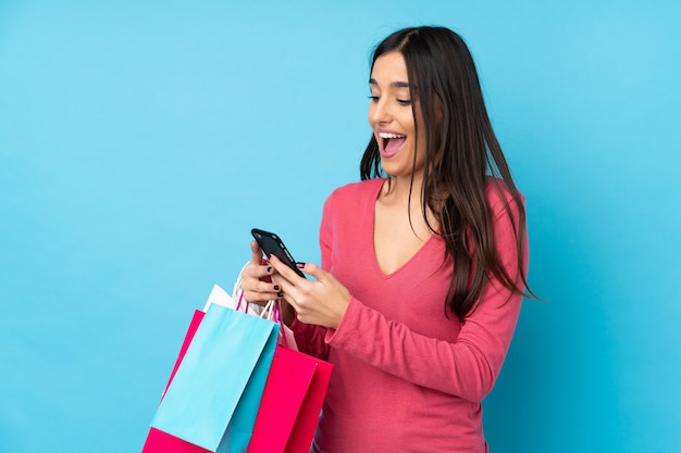Young brunette woman over isolated blue wall holding shopping bags and writing a message with her cell phone to a friend