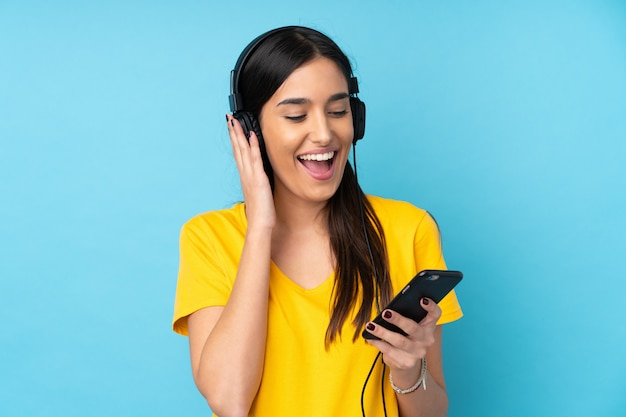 Young brunette woman over isolated blue wall listening music with a mobile and singing