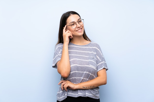 Young brunette woman isolated blue  with glasses