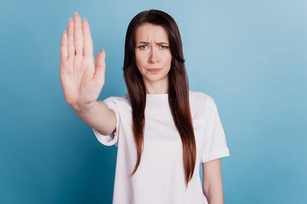 Молодая брюнетка женщина, изолированные на синем фоне, делает знак остановки ладонью