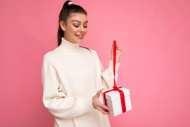Young brunette woman isolated over pink background wall wearing white sweater holding gift box and unboxing present looking at box.