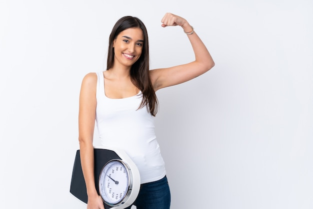 Young brunette woman over isolated white wall holding a weighing machine and doing strong gesture