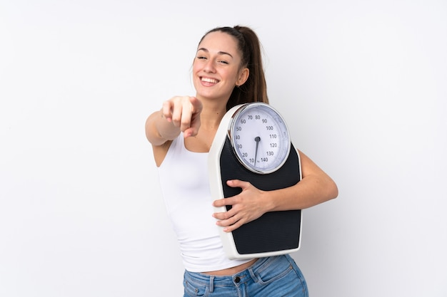 Young brunette woman over isolated white wall holding a weighing machine and pointing to the front