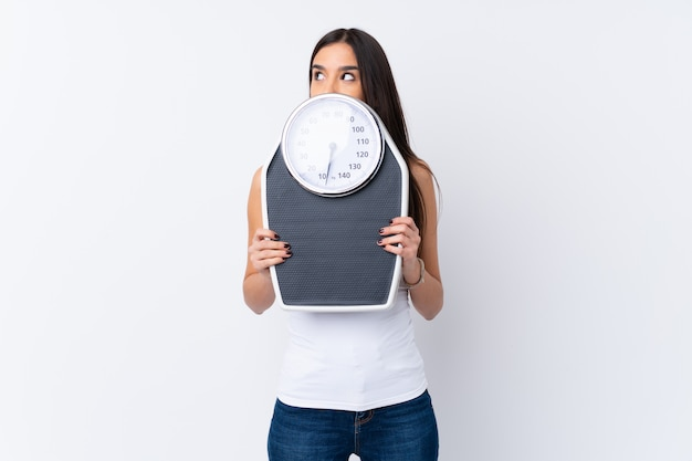 Young brunette woman over isolated white wall with weighing machine and hiding behind it