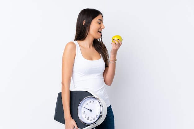 Young brunette woman over isolated white wall with weighing machine and with an apple