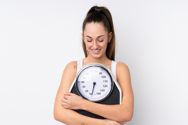 Young brunette woman over isolated white wall with weighing machine