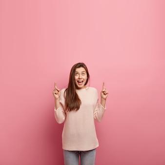 Giovane donna castana in jeans e maglione