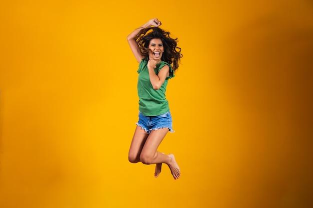 Молодая брюнетка женщина прыгает в фоновом режиме