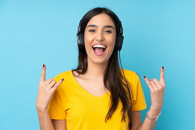 Young brunette woman listening music making rock gesture