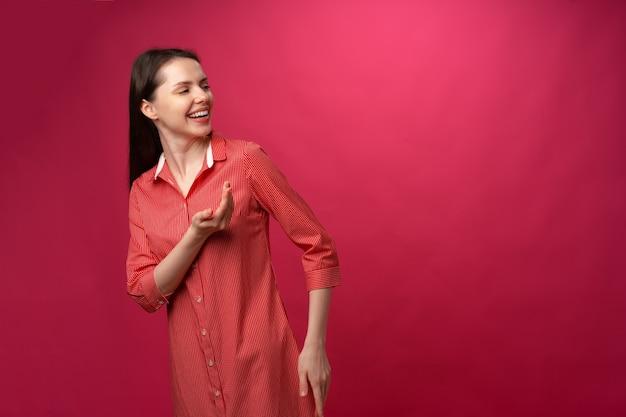분홍색 배경에 공간을 복사하기 위해 옆으로 바라보는 젊은 브루네트 여성