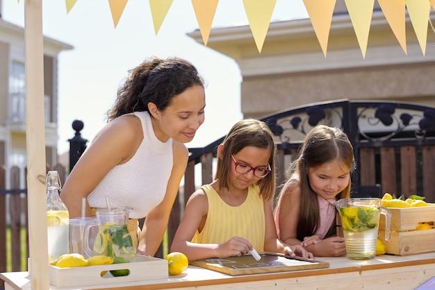晴れた日にレモネードを販売しながらチョークで小さなボード上の通知を指している娘を見ている若いブルネットの女性