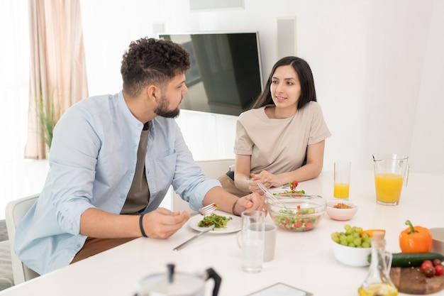 自作の野菜サラダとオレンジジュースの両方を持っている間朝食で会話中に彼女の夫を見ている若いブルネットの女性