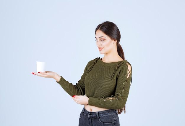 Молодая женщина брюнет смотря пластиковый стаканчик на белой предпосылке.
