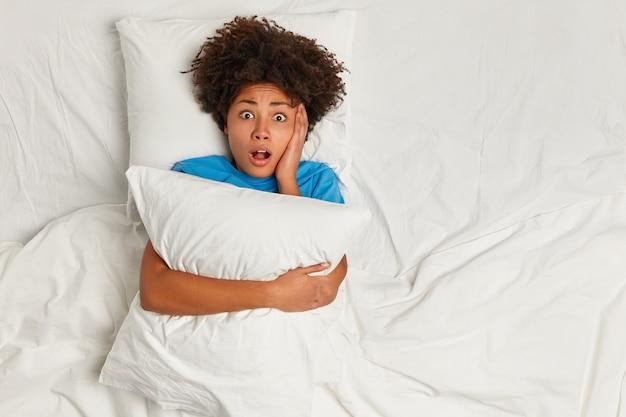 Giovane donna castana sdraiata a letto