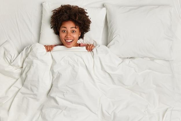 침대에 누워있는 젊은 갈색 머리 여자